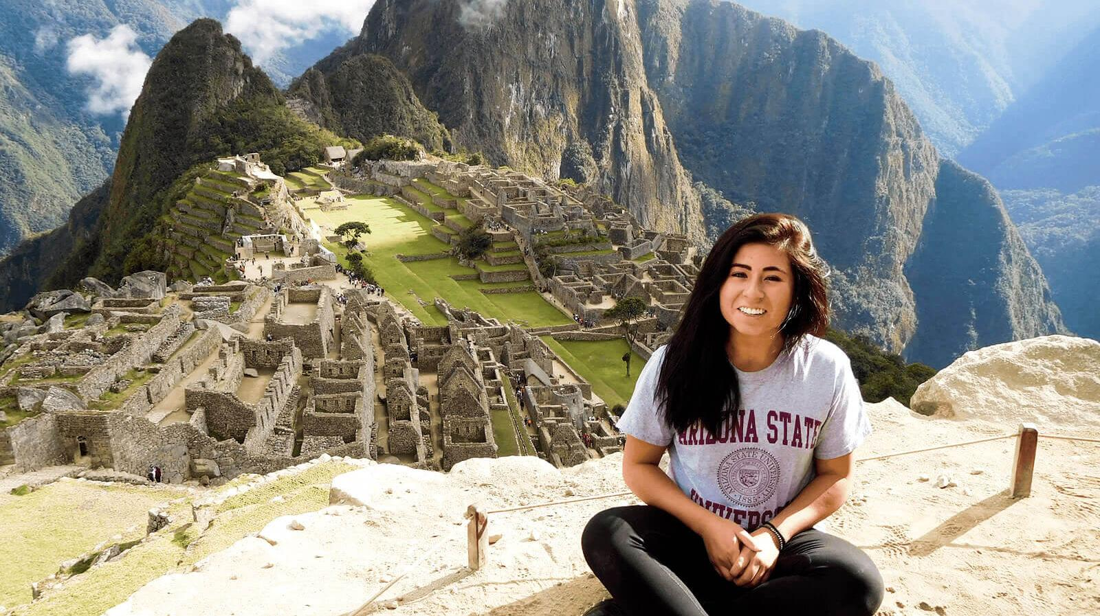 A student smiles in front of Machu Picchu