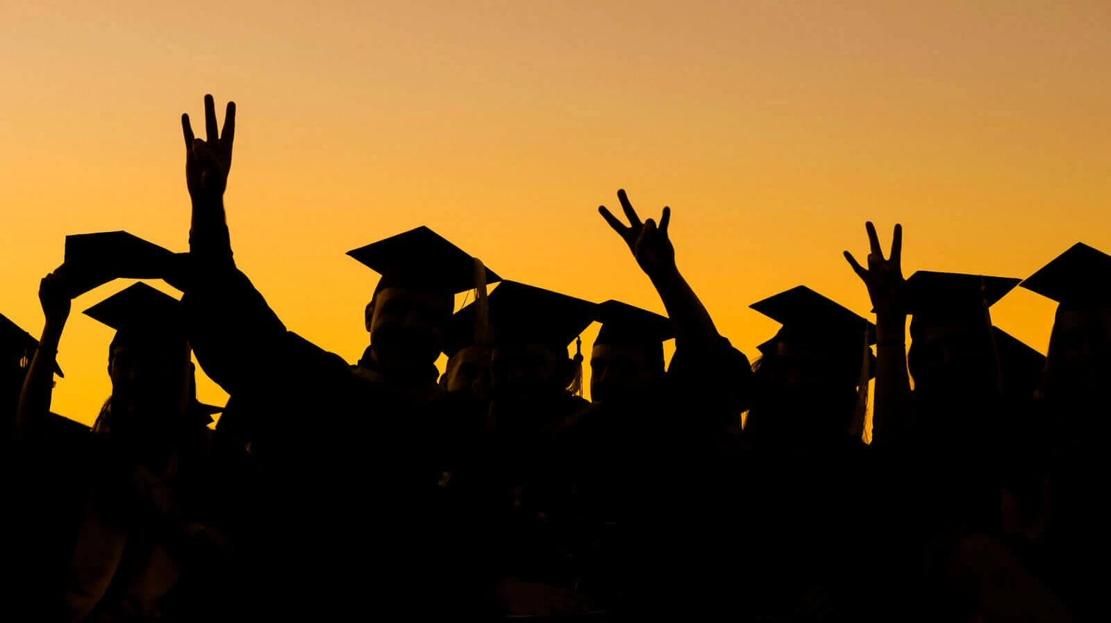 Forks up! Grads in mortarboards at dusk
