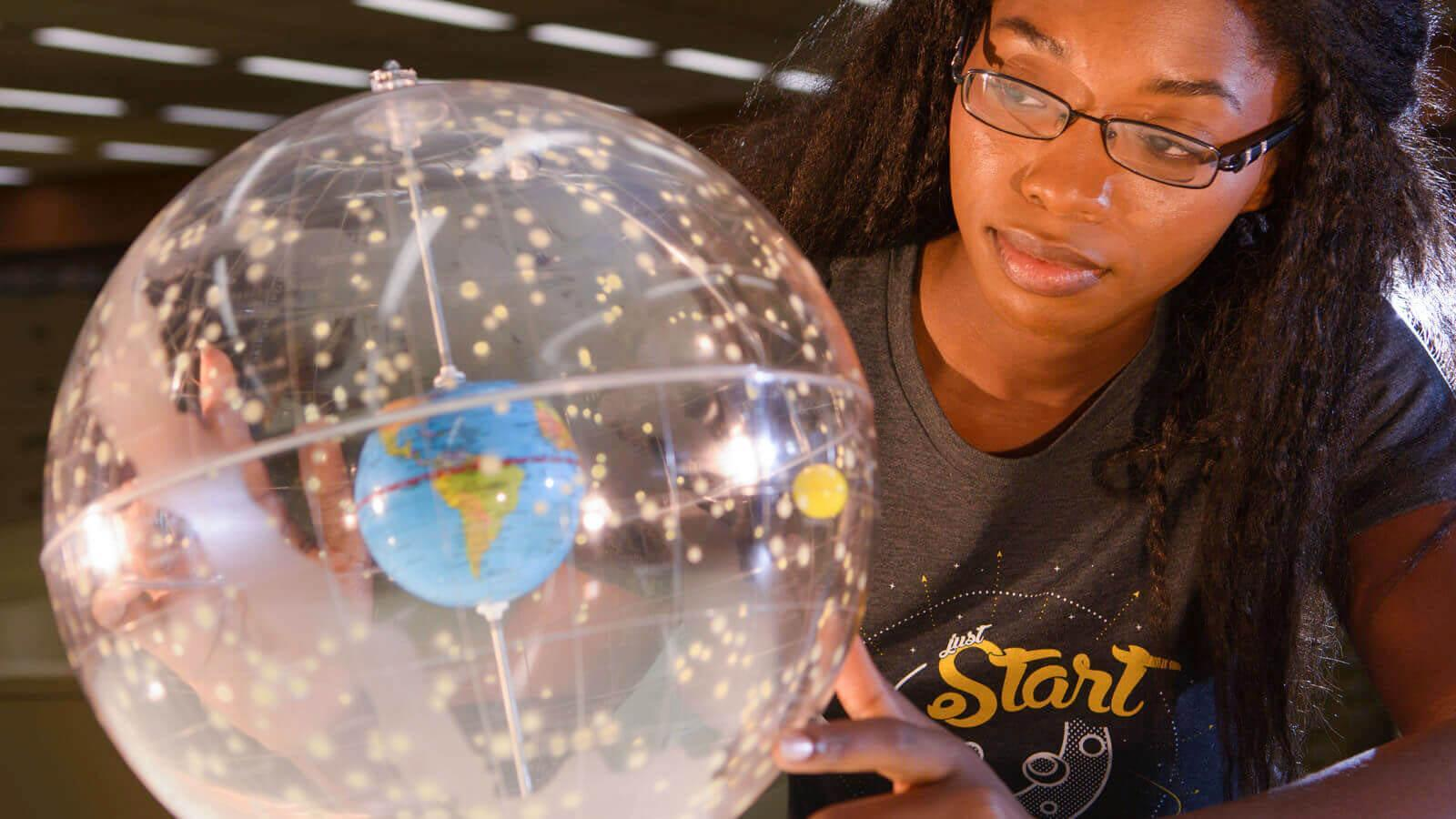 A woman looks at a globe with a star map