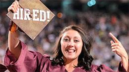 Woman pointing excitedly to her graduation cap, that reads Hired!
